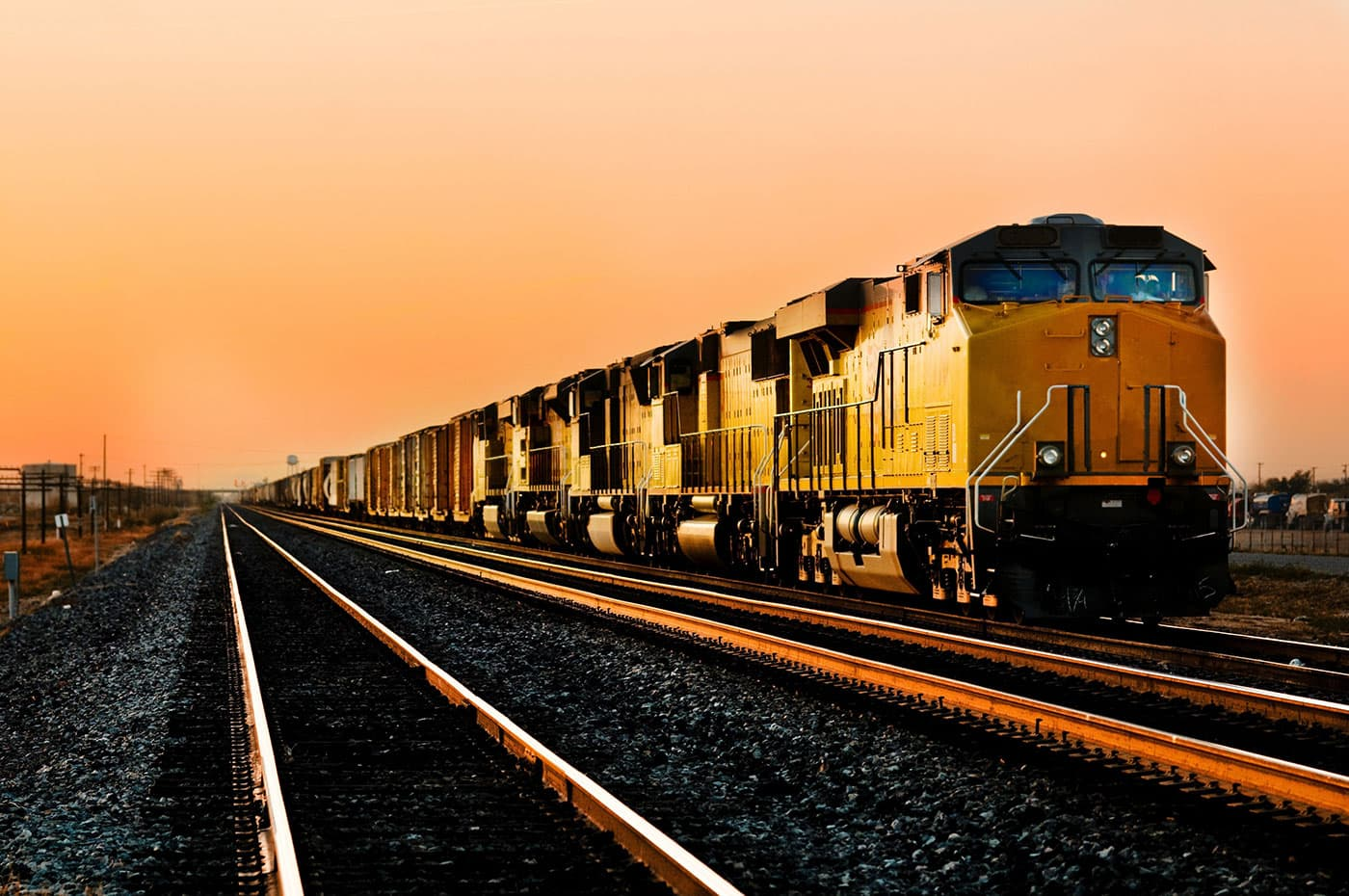 Acme OEM Transportation | Cargo locomotive railroad engine crossing the desert at sunset